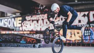 Jugendlicher macht einen Trick auf seinem BMX Rad