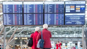 Familie steht vor Anzeigetafel an Flughafen auf der Flüge gecancelt wurden