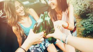 Frauen trinken Alkohol im Kofferraum eines Autos