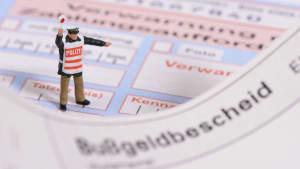 Ein Spielzeugpolizist steht auf einem Bußgeldbescheid