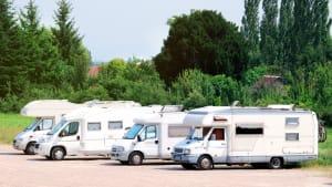 Vier Wohnmobile stehen nebeneinander auf einem Parkplatz