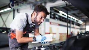 Mechaniker steht am Motor eines Autos in einer Werdkstatt und schreibt etwas auf