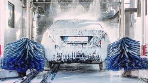 Ein silberne Limousine wird in der Waschanlage eingeschäumt