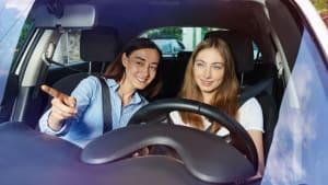 Teenagerin lernt von ihrer Mutter Auto fahren