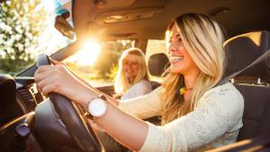 Junge Frau fährt in Begleitung von einer Frau ein Auto
