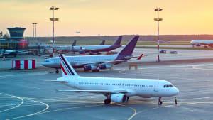 Flugzeuge stehen auf dem Rollfeld eines Flughafens im Sonnenuntergang