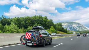 Auto mit Dachbox und Fahrrädern auf dem Fahrradträger auf der Autobahn
