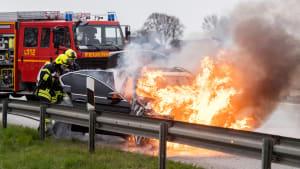 Die Feuerwehr löscht ein brennendes schwarzes Auto auf einer Landstraße