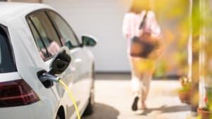 Eine Frau geht in ihr Haus während das Elektroauto aufgeladen wird