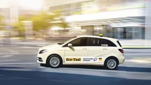 Ein Eco-Taxi fährt dynamisch auf einer Strasse in der Stadt