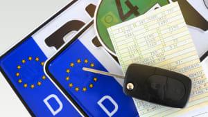 Autoschlüssel liegt auf Fahrzeugschein und Autokennzeichen