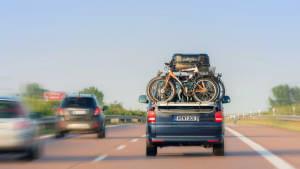 Kleinbus mit Fahrradheckträger und Dachbox fährt auf der Autobahn