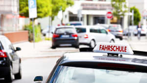 Ein Fahrschulauto ist von hinten auf einer Straße zu sehen
