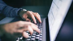 Close-Up von Männerhänden auf einer Tastatur am Laptop