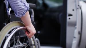 Ein Rollstuhlfahrer vor einem Auto