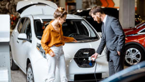 Eine Frau und ein mann stehen an einem Elektroauto