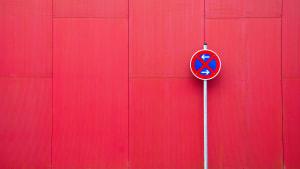 Schild mit absolutem Halteverbot vor roter Wand