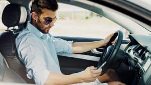 Mann schaut während der Autofahrt auf sein Handy