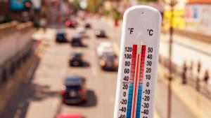 Hitze - ein Thermometer zeigt 40 Grad im Close Up im Hintergrund eine befahrene Stadtstrasse im Sommer