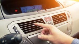 Hand an der Lüftung im Auto