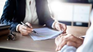 Ein Close up von Personen und Händen die an einem Glastisch verhandeln