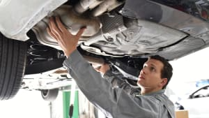 Automechaniker arbeitet am Katalysator