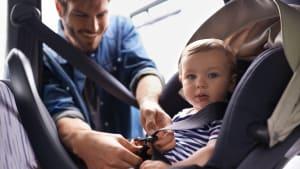 Mann schnallt sein Kind im Kindersitz an