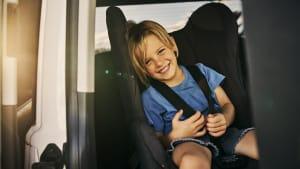 Kind sitzt lachend und angeschnallt im Kindersitz