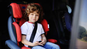 Junge sitzt angeschnallt im Kindersitz im Auto