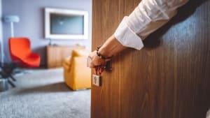 Mann öffnet Tür zu Hotelzimmer