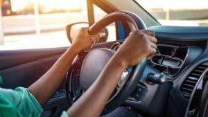 Frau sitzt im Auto und hält das Lenkrad fest