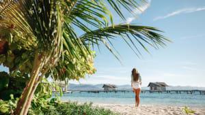 Frau steht auf einem tropischen Strand mit Kokospalmen und türkisfarbenem Meer und genießt ihren Urlaub auf den Malediven