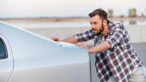Mann schiebt sein Auto nach Autopanne