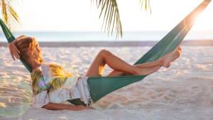 Eine Frau liegt an einem Traumstrand in einer Hängematte