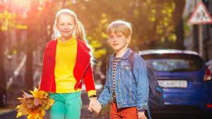Ein Mädchen und ein Junge überqueren an einem sonnigen Herbststag sicher die Srraße