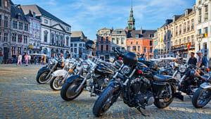 Viele Motorräder stehen auf einem Platz in einer Stadt