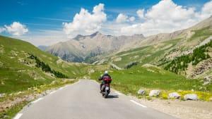 Ein Motorrad fährt auf einer Strasse durch einen Gebirgslandschaft