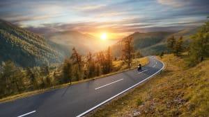 Motorradfahrer auf einer Passstraße im Herbst