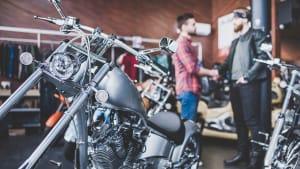 Zwei Männer in einem Motorradladen schütteln sich die Hände.
