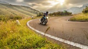 Motorradfahrer kurvt auf Landstrasse im Alpenvorland