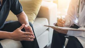 Mann spricht mit einem Arzt oder Psychologen