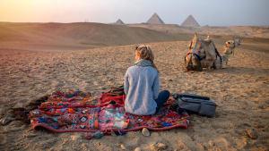 Frau sitzt auf einer Decke in der Wüste, neben ihr ein Kamel und im Hintergrund die Pyramiden von Gizeh