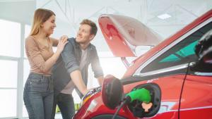 Junges Paar vor einem Elektroauto in einem Autohaus