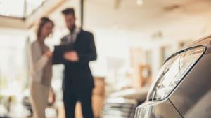 Mann und Frau stehen in einem Autosalon