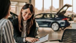 Eine Autoverkäuferin lächelt am Tisch einer Kundin beim Vertragsabschluss zu.