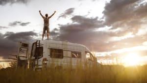 Ein Mann steht auf dem Dach seines Campingbusses am Straßenrand