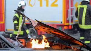 De Feuerwehr steht nach einem Unfall hinter einem brennenden Autoauf einer Straße