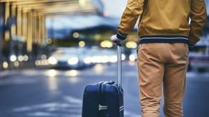 Ein Reisender steht mit einem Koffer auf einer Strasse