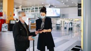 Eine Frau kontrolliert den Reiseausweis eines Mannes  am Flugahfen