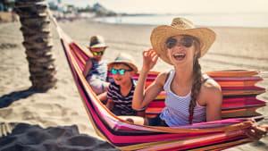 Drei Kinder sitzen in einer Hängematte an einem Strand in Spanien